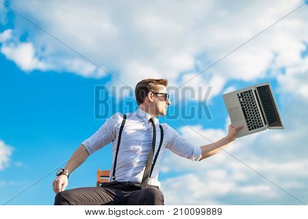 Attractive Serious Busunessman In White Shirt, Tie, Braces And Sunglasses Going To Break The Laptop