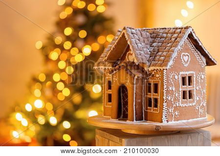gingerbread house over defocused lights of Chrismtas decorated fir tree. Christmas eve, warm atmospheric light