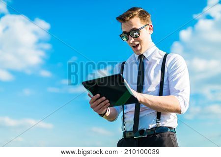 Attractive Busunessman In White Shirt, Tie, Braces And Sunglasses Look In Tablet