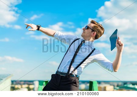 Attractive Busunessman In White Shirt, Tie, Braces And Sunglasses Throw Tablet From Roof