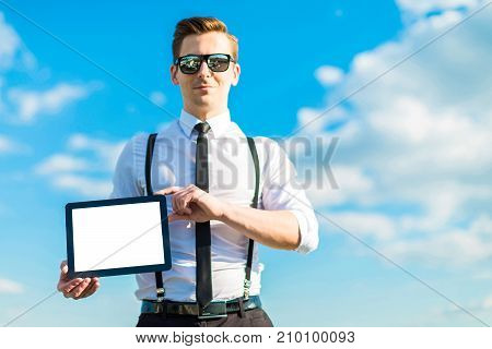 Young Busunessman In White Shirt, Tie, Braces And Sunglasses Shows Empty Tablet