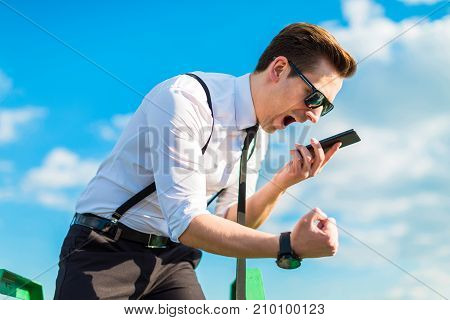 Attractive Busunessman In White Shirt, Tie, Braces And Sunglasses Stand On The Roof Ladder