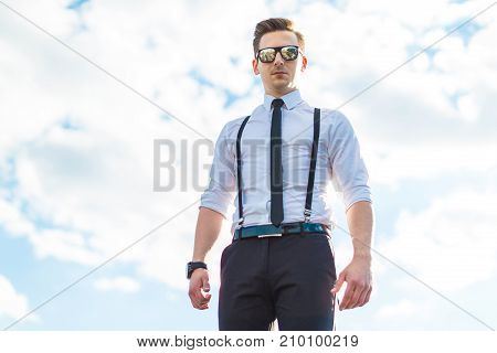Serious Young Busunessman In White Shirt, Tie, Braces And Sunglasses Stand On The Roof