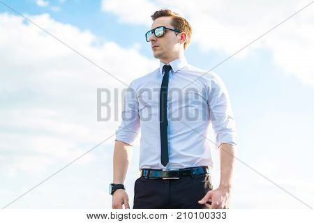 Attractive Young Busunessman In White Shirt, Tie And Sunglasses Stand On The Roof