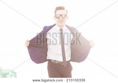 Attractive Young Busunessman In Blue Suit And Sunglasses Stand On The Roof