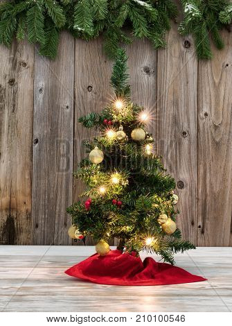 Christmas Tree decoration on rustic wooden boards with evergreen branches in background