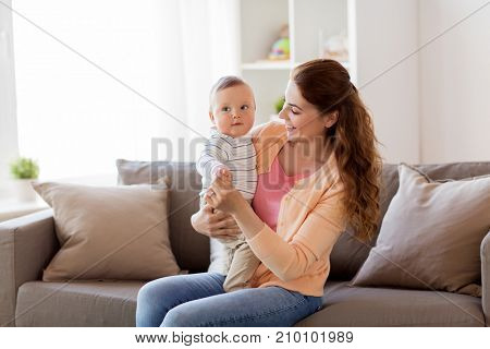 family, child and motherhood concept - happy smiling young mother with little baby at home