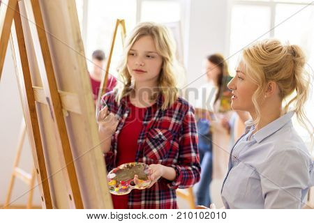 creativity, education and people concept - artists or student girl with palette and painting knife and teacher discussing picture on easel at art school studio