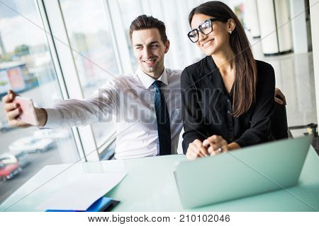 Two Colleagues Friends Taking The Picture To Them Self Sitting In The Office, Man And Woman Taking S