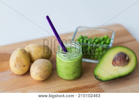 baby food, healthy eating and nutrition concept - glass jar with green vegetable puree on wooden cutting board