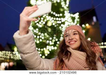 holidays and people concept - beautiful happy young woman taking selfie over christmas tree lights in winter evening