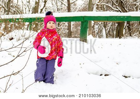 Little cute caucasian girl in a beautiful warm handmade knitted hat with fluffy fur pom pom walking in a city park at bright winter day.