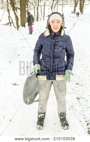 Beautiful caucasian girl laughing and having fun riding a saucer sled downhill in a forest or city park. Showing her resent after the pants got dirty after downhill.
