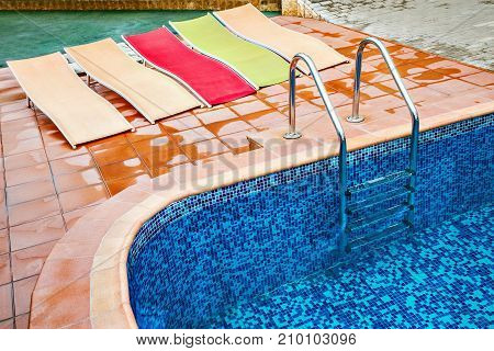 Five chaise-longues by the swimming pool on the hotel territory.