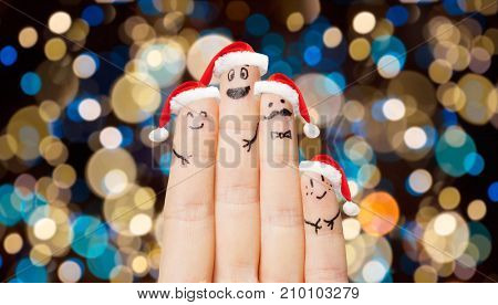 christmas, holidays, family and body parts concept - close up of four fingers with smiles in santa hats over lights background