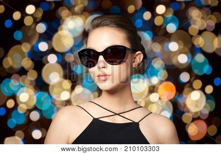 accessories, fashion, people and luxury concept - beautiful smiling young woman in elegant black sunglasses over holidays lights background