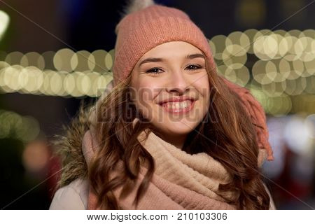 holidays and people concept - portrait of beautiful happy young woman over christmas lights in winter evening