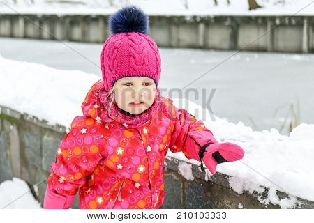 Little Cute Caucasian Girl In A Beautiful Warm Handmade Knitted Hat With Fluffy Fur Pom Pom Walking