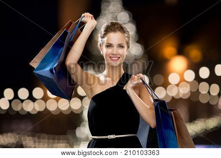 sale, fashion, people and luxury concept - happy beautiful young woman in black dress with shopping bags over christmas tree lights background