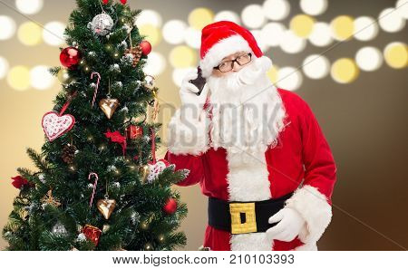 holidays, technology and people concept - man in costume of santa claus and christmas tree calling on smartphone