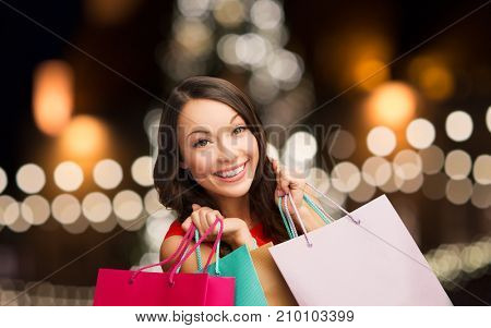 sale, holidays and people concept - smiling woman with shopping bags over christmas tree background