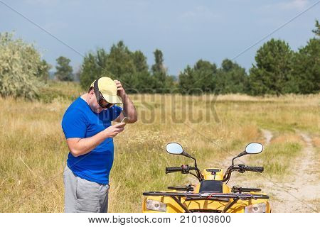 A caucasian man riding an ATV vehicle over rough terrain lost his path in an autumn pine forest and using navigation electronic device in his hand to find the right way.
