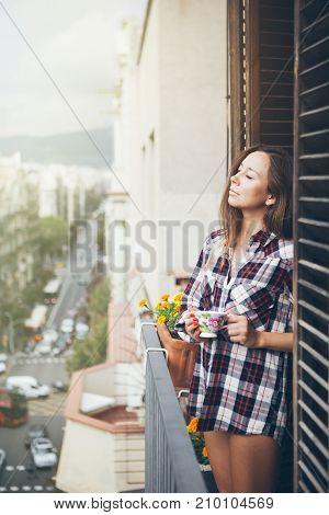 Beautiful young woman is drinking cup of coffee or tea while standing on the balcony dressed only in one paid shirt. Sun light flair effect.