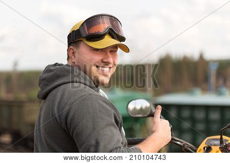 Caucasian Man In Sport Protective Goggles And Yellow Cap Riding An Atv Over Rough Terrain Enjoying H