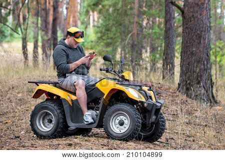 A caucasian man riding an ATV vehicle over rough terrain lost his path in an autumn pine forest and using navigation electronic device in his hand to find the right way. poster