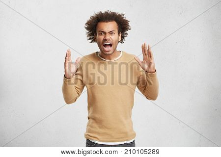 Waist Up Portrait Of Furious African American Male Gestures In Anger, Being Dissatisfied With Result