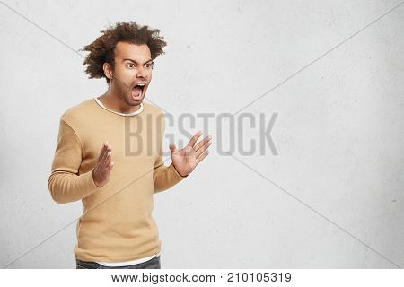 Horizontal Portrait Of Furious Dark Skinned Man Has Crisp Hair, Wears Casual Clothes, Screams Angril