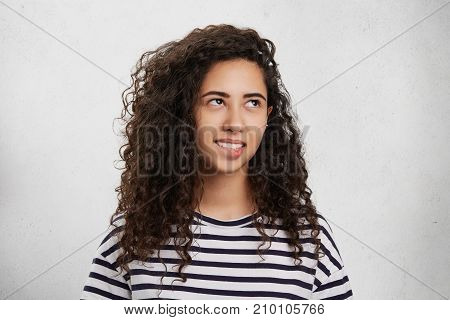 Brunette Curly Mixed Race Woman Bites Lower Lip As Being Uncertain And Frustrated, Has Thoughtful Ex