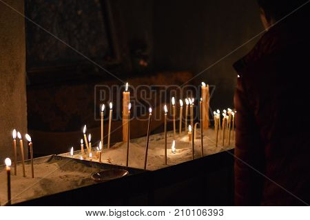 Prayer place with candles in the church. Wax burning candles burning create a smooth warm light.