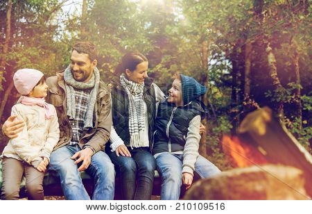 camping, travel, tourism and hike concept - happy family sitting on bench and talking at camp near campfire in woods