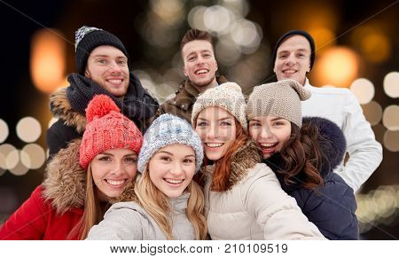 friendship, holidays and people concept - group of happy friends taking selfie outdoors over christmas lights background