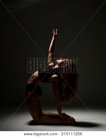 Beautiful caucasian female athlete stretching on a floor. Young woman in sportswear in gym work out on dark background