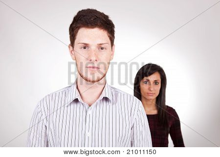 Upset couple after an argument man in front poster