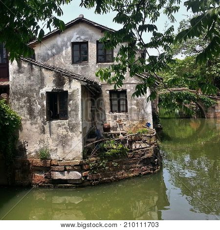 Venice of the East - Zhouzhuang water town in China. An old house in the bank of the stream in the Zhouzhuang water town in Jiangsu province in China.