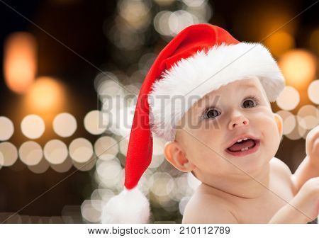 christmas, holidays and people concept - close up of happy little baby boy or girl in santa hat over lights background