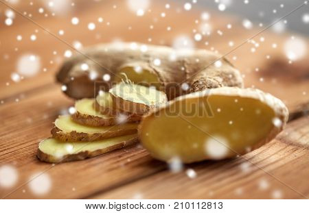 ethno science, culinary, diet, eco food and objects concept - close up of ginger root on wooden table over snow