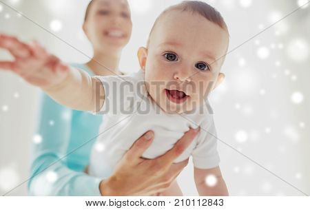 family, child and babyhood concept - close up of happy smiling young mother with little baby over snow