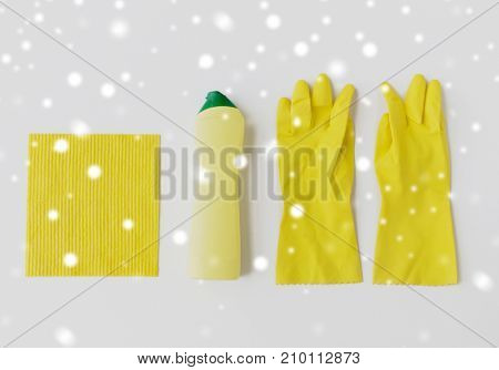 cleaning stuff, housework, housekeeping and household concept - bottle of detergent, rubber gloves and rag on white background over snow