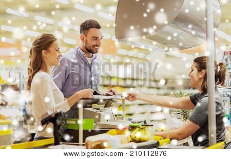 shopping, sale, consumerism and people concept - happy couple buying food at grocery store or supermarket cash register over snow