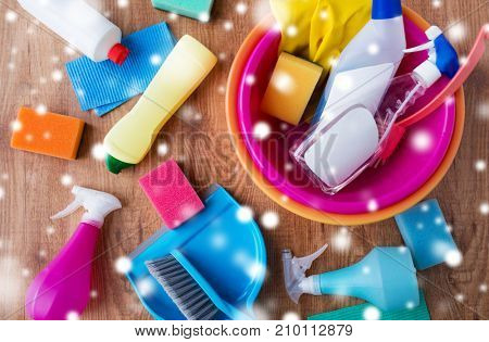 housework, housekeeping and household concept - basin with cleaning stuff on wooden floor over snow
