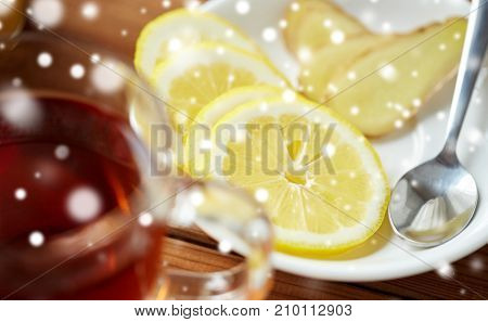 health, traditional medicine, folk remedy and ethnoscience concept - tea cup with lemon and ginger on plate with spoon over snow