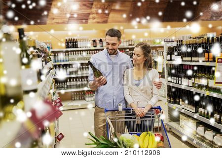 sale, consumerism, alcohol and people concept - happy couple with bottle of white wine and food in shopping cart at liquor store or supermarket over snow