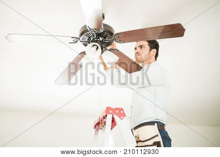 Man In Ladder Fixing Ceiling Fan