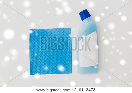 cleaning stuff, housekeeping and household concept - bottle of detergent on toilet cleaner and blue rag on white background over snow