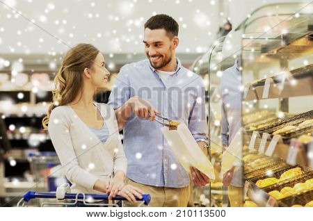 food, sale, consumerism and people concept - happy couple with shopping cart at grocery store or supermarket baking department buying buns or pies over snow