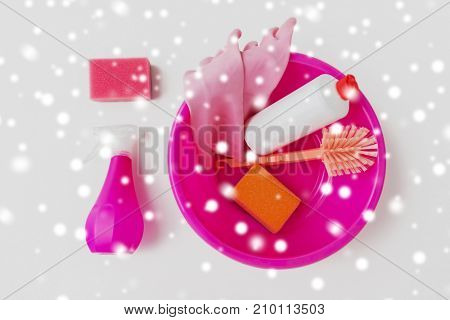 housework, housekeeping and household concept - pink basin with cleaning stuff on white background over snow